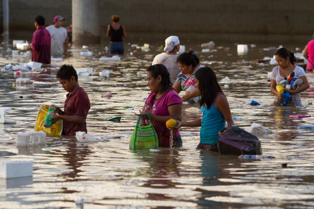 Acapulco Sep 18 2013. Una familia busca restos de comida en el agua. El municipio de Acapulco se vió severamente afectado tras el paso del huracán Manuel .