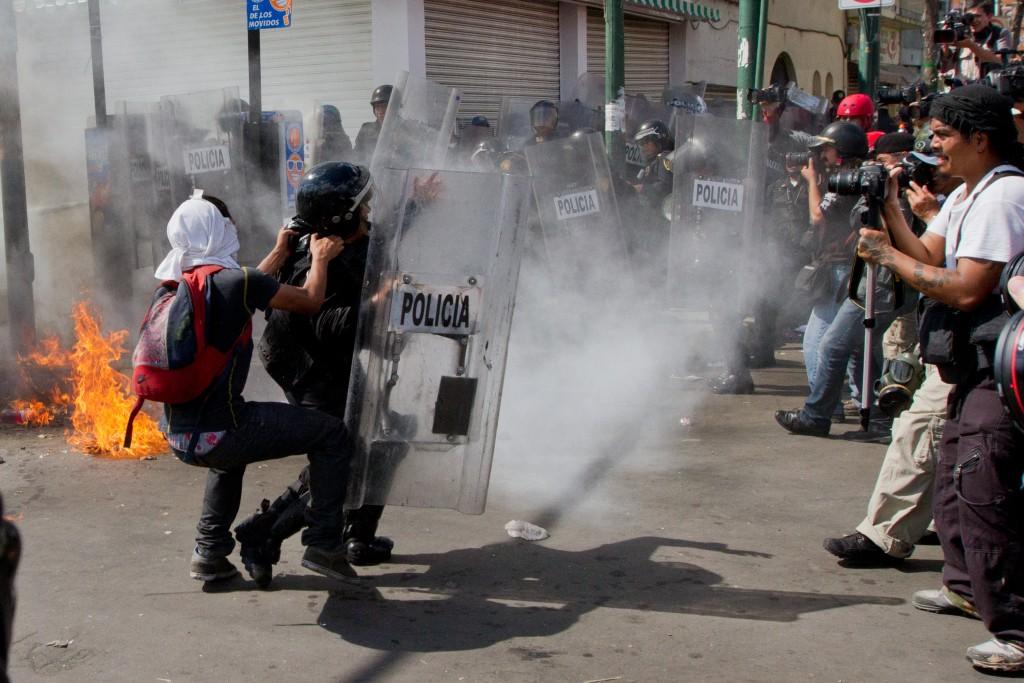 México Sep 01 2013. Un manifestante de los denominados anarquistas jalonea a un policia antimotin de la SSPDF durante las protestas de este día por el informe presidencial de Enrique Peña Nieto, a las afueras de la cámara de Diputados.